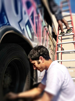 Ali Naghdali, one of about 20 volunteers, works on detailing the bus tires. Courtesy photo.