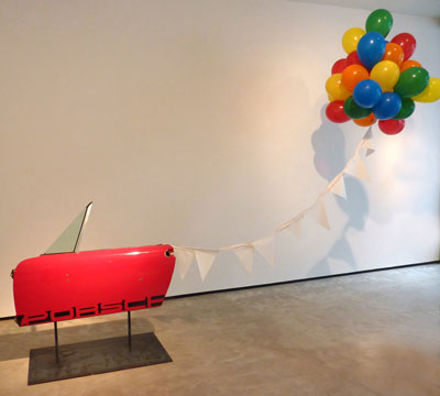 Debra Barrera, Porsche Party, 2012. 1975 Porsche 914 door, steel, pennants, balloons, helium, dimensions variable. Courtesy the artist, Texas Biennial and Moody Gallery.