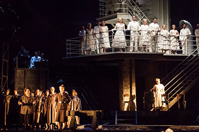 The cast of The Passenger look on from the ocean liner above and Auschwitz camp below in The Passenger at Houston Grand Opera. Photo by Lynn Lane.
