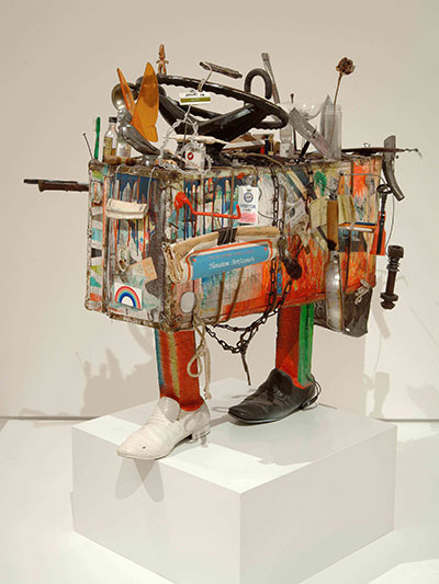 Bert L. Long, Jr.  Quest, 1983  Acrylic on suitcase with frying pan, shoes, glass, liquor bottles,  orange peel, name tag, credit card, chain, rope, steering wheel,  wood, newspaper, bone, keys, harmonica, toothbrush, and  other mixed media Image courtesy Deborah Colton Gallery