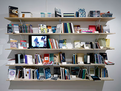 Bookshelf and still from video-poem by Stalina Villarreal, Antena @ Blaffer, Blaffer Art Museum, Houston Photography: Thomas DuBrock; Courtesy Blaffer Art Museum.