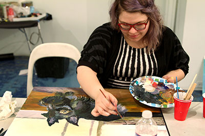 Andi Harman paints a Dubya knockoff during The Paintings of *George W Bush at CentralTrak: The University of Texas at Dallas Artist Residency.