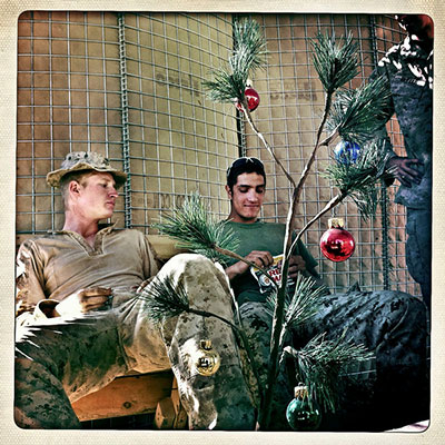 US Marines from Bravo Company's Third Platoon, with the First Battalion, Eighth Marines, sitting around a Christmas tree with Female Engagement Team members at the Sher Ghazi base in Helmand Province, Afghanistan, on November 9, 2010. Note that these images combine four separate photographs and that only one Christmas tree actually existed.