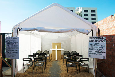 "Installation view of the ""Revival Tent"" from New New Berlin by William Powhida and Jade Townsend, 2014. Photo by Kitty Joe Sainte-Marie."