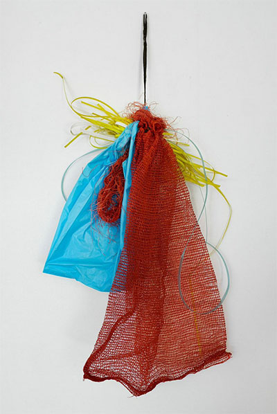Tony Feher, Preliminary Aspect, 2001 Red onion bag with black draw string, blue plastic tee shirt bag and blue, white, and yellow plastic strapping 36 x 26 1/2 x 4 Courtesy Hiram Butler Gallery.