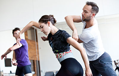 Choreographer Garrett Smith works with Houston Ballet dancers Katharine Precourt and William Newton. Photo by Amitava Sarkar.