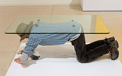 Alejandro Diaz, Muebles (Table), 2015. Cast resin, paint, clothing, hair, glass. 62x32x21 inches.