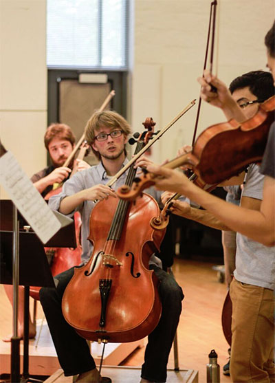 Cellists Max Geissler (foreground) and Nathan Watts (background), in rehearsal for KINETIC.