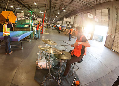 Composer Graham Reynolds accompanies a quintet of forklifts in Goodwill Central Texas warehouse for Forklift Danceworks RE Source. Photo by Amitava Sarkar.