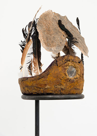 Harold Mendez, Margarita, 2016. Reclaimed foam from a baseball batting helmet, broken glass, dried foliage, owl, rooster and vulture feathers from El Astillero, Zacatecas, Mexico and steel, 81 x 12 x 12 in. Photograph by Aron Gent, courtesy of the artist and Patron Gallery, Chicago.