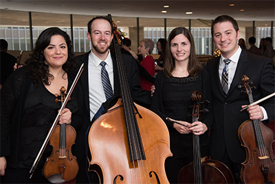 The 2015-16 Community-Embedded Musicians: Jenna Barghouti, David Connor, Hellen Weberpal, Tony Parce) pose with their instruments before a family concert. Photo by Jeff Fitlow.